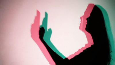 Red, green, black silhouette of woman with phone