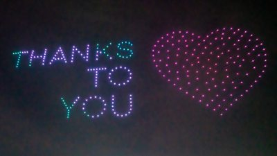 "Lights in the sky spell out ""thanks to you"" with a heart symbol"