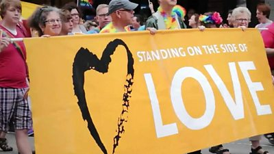 "People holding a banner saying ""Standing on the side of love"""