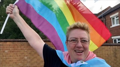 Julie Bremner holding the rainbow Pride flag