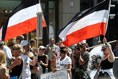 Protesters carry the flag of the pre-World War One German Empire at the Berlin protest