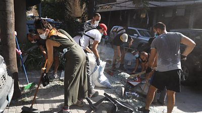 People clean up the aftermath in Beirut