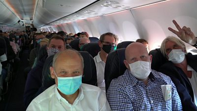 Masked passengers on a plane