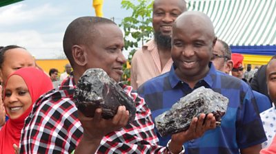 Saniniu Laizer, owner of a Tanzanian mining company, with a large Tanzanite gemstone in each hand