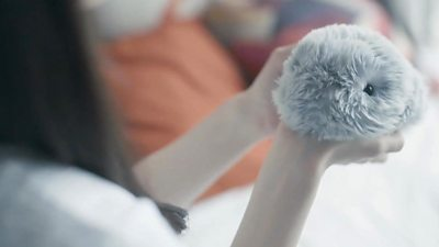 A person holds a robo-pet called Moflin
