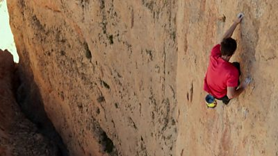 A man free solo climbing (climbing without ropes)