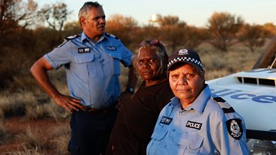 Two Indigenous police officers with Aboriginal elder