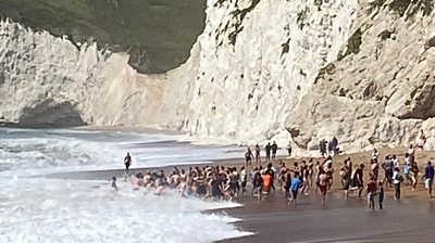 More than 20 people linked arms to enter the sea at Durdle Door and bring a swimmer back to shore.
