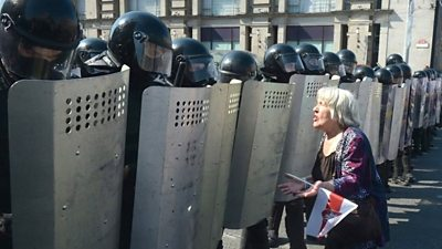 A woman protester faces off against riot police