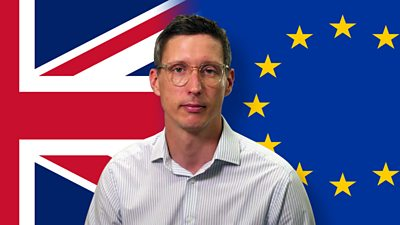 Jonathan Blake in front of UK and EU flags