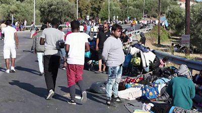 Migrants from Moria camp huddled on road