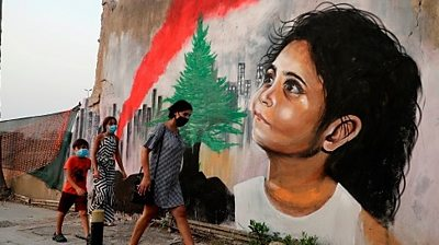 Pedestrians walk past a mural painting depicting a young Lebanese girl who suffered a face injury in the Beirut port blast