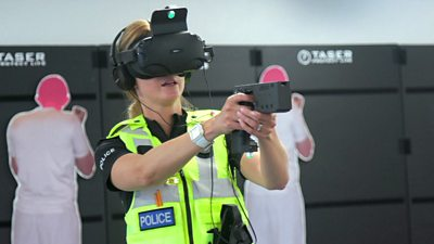 A police office wearing a virtual reality headset and gun