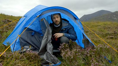 Mike Corey sits in a blue tent on the Isle of Skye