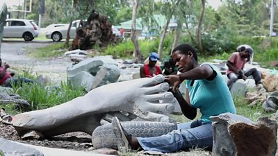 An artist working on the sculpture of a foot in Zimbabwe