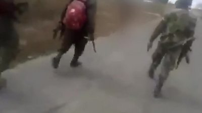 Still from video showing men walking on road