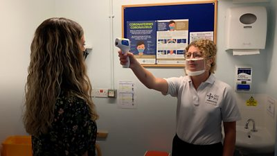 An audiologist wearing a clear face mask