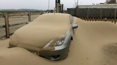 Car covered in sand