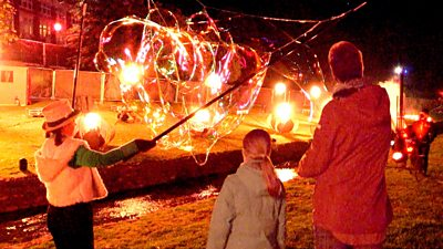 Three people watching a fire display