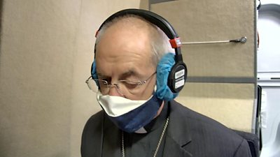 Justin Welby in a radio studio wearing a face mask