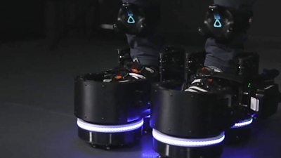 A close up of someone wearing a pair of robotic VR shoes