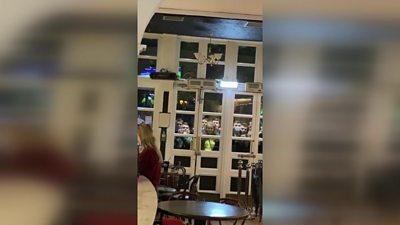 Fans watch football through pub window