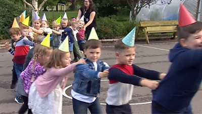 Children doing the conga line at a school birthday party