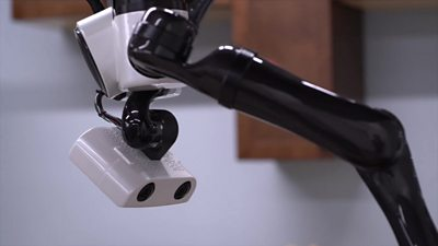 A robot head and robotic arm appear from the ceiling