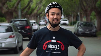 Man standing in street wearing bike helmet