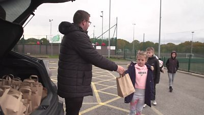 Man handing out lunch bag to child