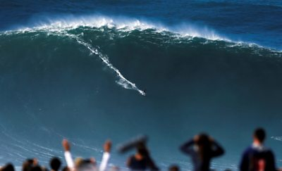 A surfer rides a large wave at Praia do Norte in Nazare