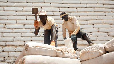 Two men using moon bricks to build a school
