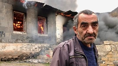 Man standing in front of burning house