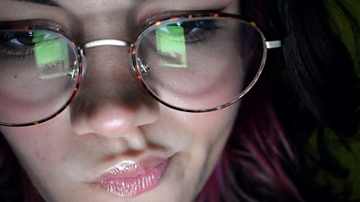 A picture of a young woman wearing glasses, in the reflection you can see a mobile phone
