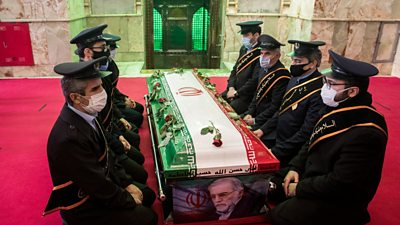 Mourners sit next to the coffin of Iranian nuclear scientist Mohsen Fakhrizadeh