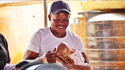 A man holding a toy baby and smiling