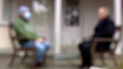 two men sitting in garden soft focus