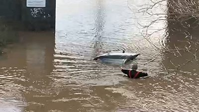Fireman approaches car in flood water