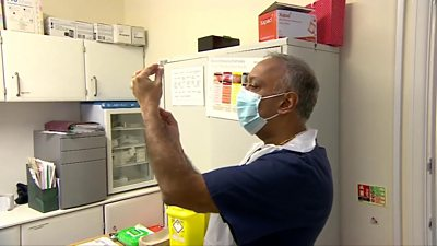 Dr Anil Mehta holds up a needle containing the Covid-19 vaccine.