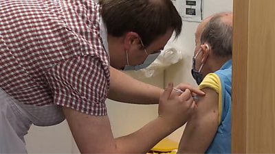man receiving vaccine at pharmacy