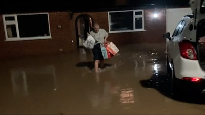 Woman carrying bags from her home in flooding