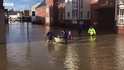 A care worker is helped through flood water