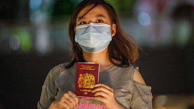Woman holding BNO passport