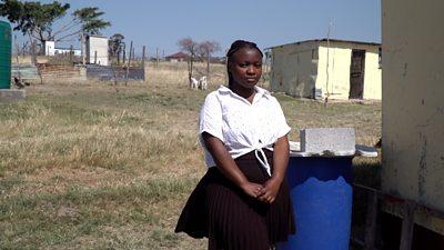 Yolanda standing in front of her home