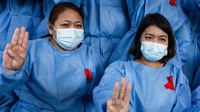 Female healthcare workers in Myanmar showing the three-fingered salute