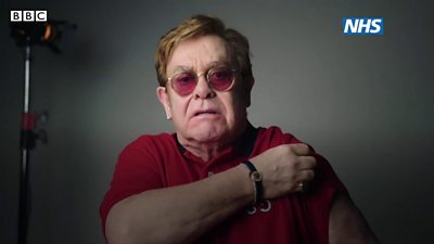 Elton John lifts up his sleeve to receive the vaccine.