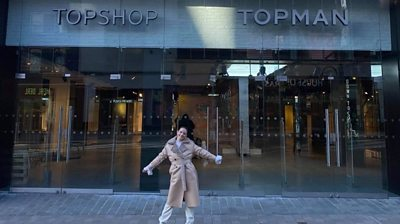 A Topshop employee outside a store