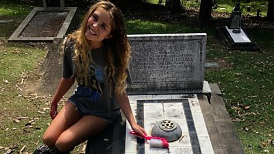 Girl sitting on grave with cleaning brush