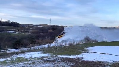 A train snowplough is filmed in action near Huntly.