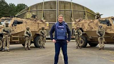 BBC Technology reporter Zoe Kleinman stands in front of military personnel at RAF Honington